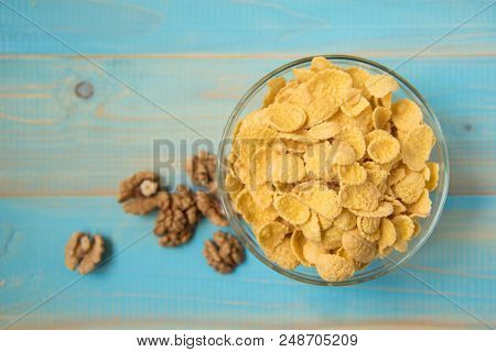 Tasty Cornflakes Witt Walnut In Glass Bowl On Blue Background. Top View