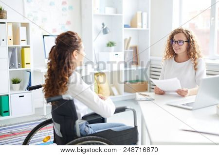 Young employer and woman in wheelchair sitting in front of one another and talking during interview