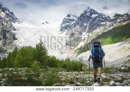 Hiker Trekking In The Mountains. Climber With Tourist Backpack Goes To Rocky Mountain Covered With S