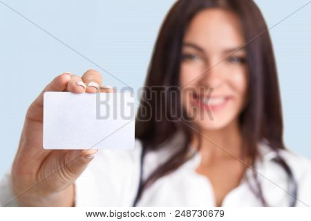 Horizontal Shot Of Medical Worker Holds Blank Card, Blurred Silhouette, Free Space For Your Name And