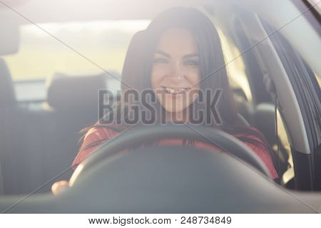 Happy Professional Female Driver Looks Through Windshiled, Drives Car, Being In Good Mood As There I