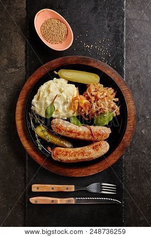 Traditional German Sausages with Mashed Potato and Sauerkraut. Wurst or Bratwurst with Fermented Cabbage, Pickled Cucumbers, and Spices in Rustic Wood Bowl on Natural Black Stone Background Top View