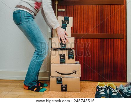 Paris, France - Jan 13, 2018: Stack Of Amazon Prime Packages Delivered To A Home Door Woman Trying T
