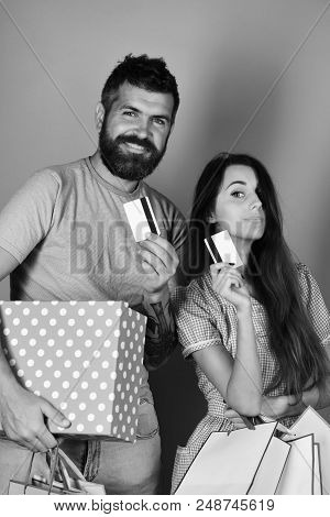 Couple In Love Holds Shopping Bags On Red Background. Guy With Beard And Girl With Pleased Faces Do