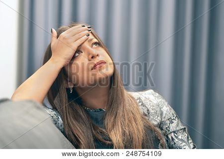 Lonely Woman Is Sad Sitting On The Bed. Portrait Of A Beautiful Sad Girl Closeup. Woman Feel Depress