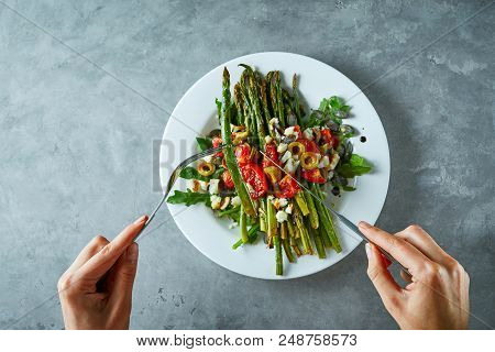 First Person View On A Dish With Roasted Asparagus, Tomatoes, Olives, Cheese And Arugula. Plate With