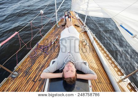 Young European Man Sitting On Yacht Looking At Sea. Travelling On Old Boat With Sail. Concept Of Fre