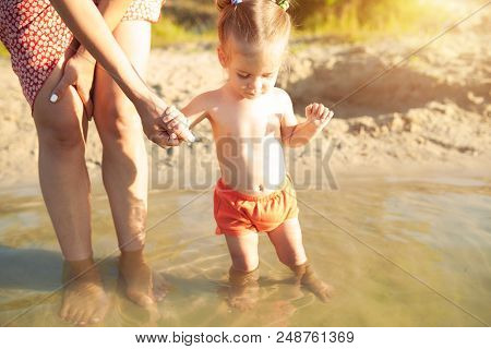 A Young Unrecognizable Mother Holding A Little Baby Girl Who Learns To Swim. Concept Of Summer Famil