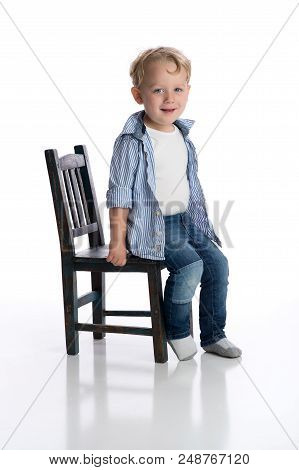 Smiling Boy Sitting On A Child's Chair