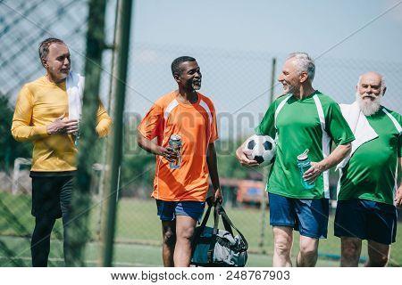 group of interracial elderly sportsmen with sportive water bottles walking on football field poster