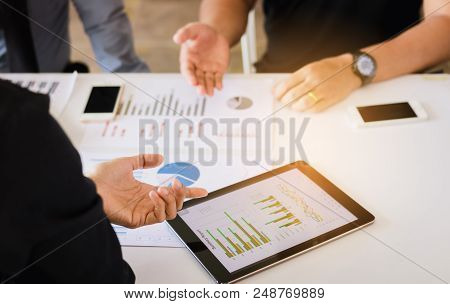 Manager And Employee Analyzing With Tablet Pc At Business Meeting With Discussion Working Together.