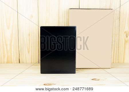 Blank Black Box And Blank Brown Box On Wooden Table.zoom In And Vertical