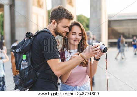 Young Couple Of Travelers Looking At Photo Camera At Pariser Platz, Berlin, Germany