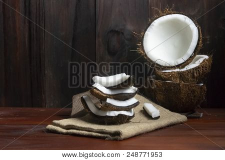 Coconut Half With Coconut Pieces On Wooden Table