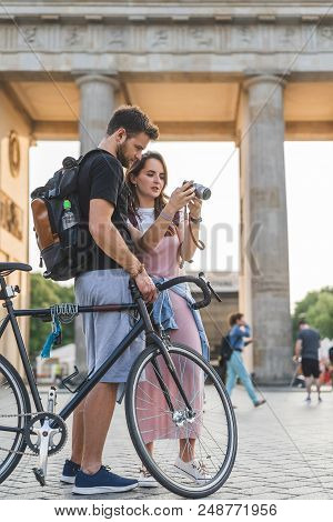Young Female Traveler Showing Photo Camera To Boyfriend With Bicycle At Pariser Platz, Berlin, Germa