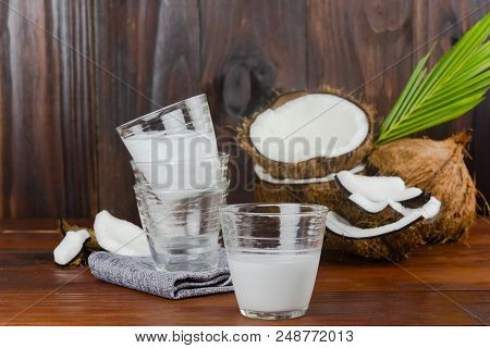 Coconut Milk Glass With Coconut Half And Coconut Pieces And Leaf  On Wooden Table .close Up.