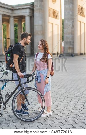 Young Couple With Bicycle And Rucksacks Talking To Each Other At Pariser Platz, Berlin, Germany