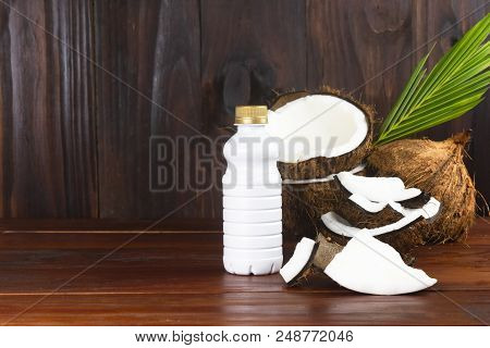 Coconut Milk Bottle With Coconut Half And Coconut Pieces And Leaf  On Wooden Table.
