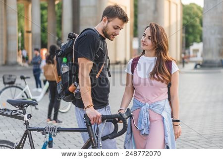 Couple Of Tourists With Backpacks And Bicycle At Pariser Platz In Berlin, Germany