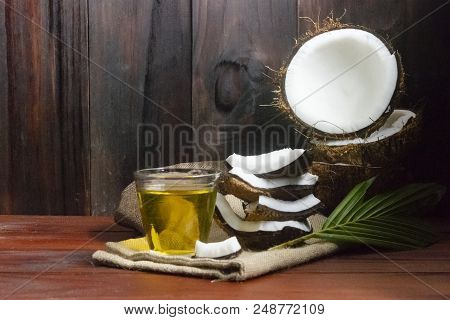 Coconut Oil With Coconut Half And Coconut Pieces And Leaf  On Wooden Table And Black Wooden Backgrou
