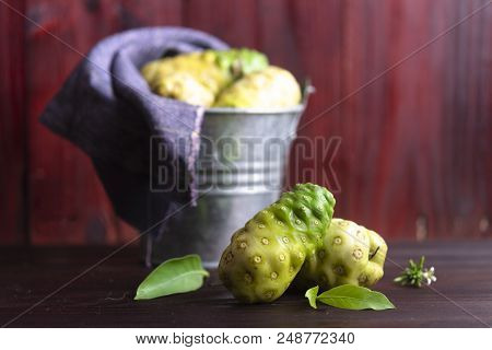 Noni Fruit And Leaves And Noni In Tank On Wooden Table.