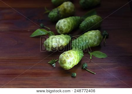 Noni Fruit And Leaves On Red And Brown Wooden Right Corner.1