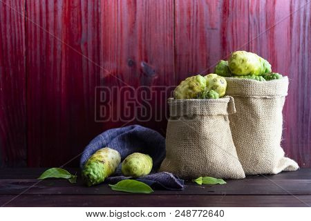 Noni In Sack  And Noni With Leaves On Wooden Table And Red Wooden Background