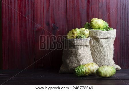 Noni In Sack  And Noni With Leaves On Wooden Table And Wooden Background