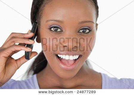 Nahaufnahme von überrascht aussehende junge Frau am Telefon auf weißem Hintergrund