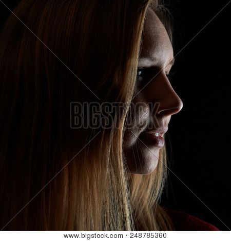 Young blond smiling woman looks sideways in the dark