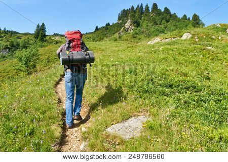 Man is hiking on hiking trail in the French Alps in summer