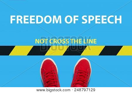 Legs In Red Sneakers On A Blue Background A Restrictive Yellow And Blak Stripe With Text Not Cross T