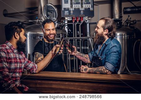 Three Bearded Interracial Friends Drink Craft Beer And Talk In A Brewery. Two Hipster Workers In Apr