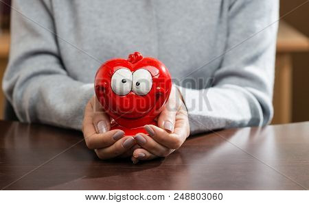 Funny Red Moneybox In Woman Hands. Concept Of Future, Business, Saving Money, Economy And Investment