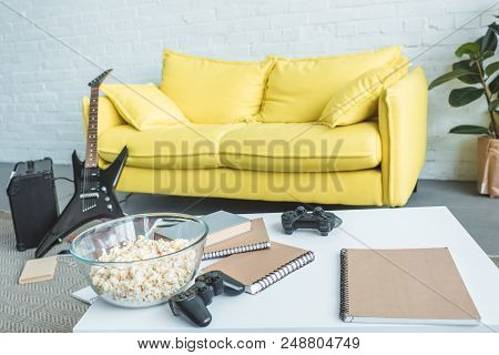 Popcorn, Joysticks And Copybooks On Table, Electric Guitar Near Couch Behind
