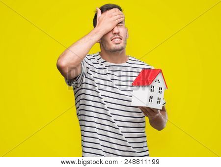 Handsome real estate agent holding a house stressed with hand on head, shocked with shame and surprise face, angry and frustrated. Fear and upset for mistake.