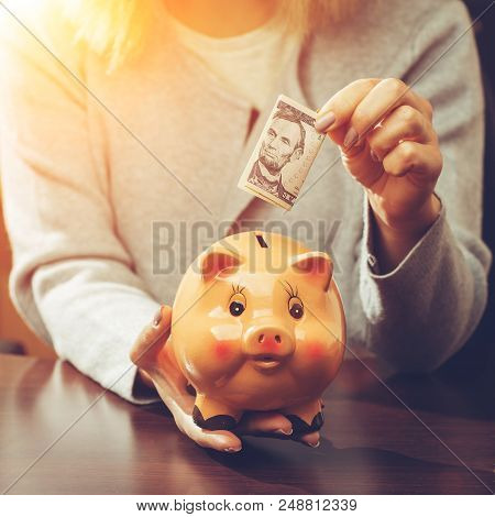 Woman Putting One Hundred Dollar Banknote In A Funny Red Moneybox In Rays Of The Sun, Toned Image. C