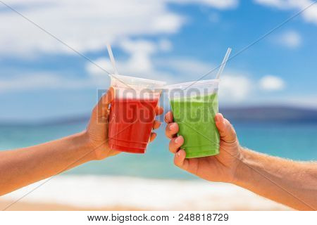 Healthy juice smoothie drinking couple toasting cold pressed organic drinks together at beach restaurant. Detox smoothie drink toast at summer vacations holidays. Fruit juicing weight loss diet.