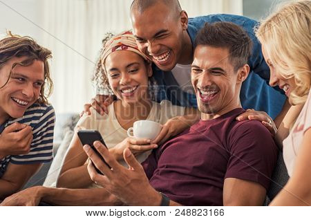 Joyful man showing video on his mobile phone with friends. Group of cheerful young men and women laughing while looking at smartphone at home. Multiethnic people sitting on sofa having fun together.