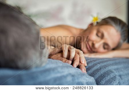 Mature couple holding hands during romantic massage at wellness center. Closeup hands of senior man and woman in salon spa after beauty treatment. Couple lying on massage table at spa.