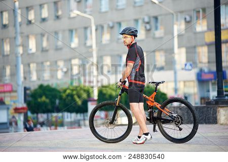 Young Man In Relaxing After Bike Ride Standing Near Bicycle In Front Of City Building. Cyclist Looki