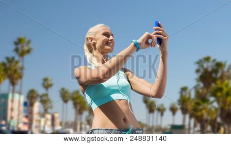 sport, technology and healthy lifestyle concept - smiling young woman with smartphone, earphones and fitness tracker listening to music over venice beach background in california poster