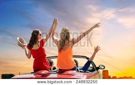 summer holidays, road trip and travel concept - happy friends driving in convertible car at country and waving hands over sky background