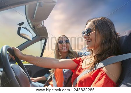 summer holidays, road trip, vacation, travel and people concept - happy young women driving in convertible car and laughing over sky background