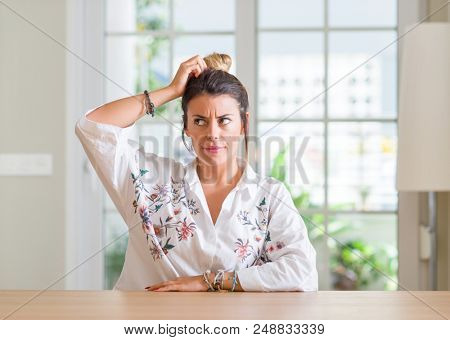 Young woman at home confuse and wonder about question. Uncertain with doubt, thinking with hand on head. Pensive concept.