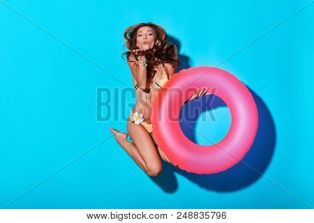 Time To Have Fun. Playful Young Woman In Bikini Blowing A Kiss And Looking At Camera While Hovering