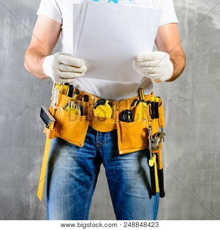 Unidentified Handyman Standing With A Tool Belt With Construction Tools And Holding Project Plan Aga