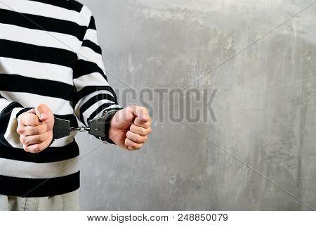 Side View Of Unidentified Prisoner In Prison Stripped Uniform Standing In The Dark Interrogation Roo