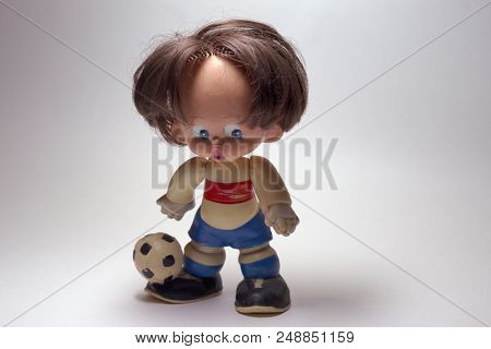 Toy Football Player, With Open Mouth. Vintage-style Uniform. Classic Soccer Ball On Toe Of The Socce
