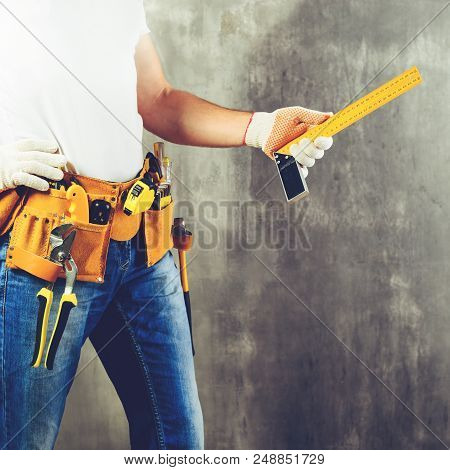 Unidentified Handyman Standing With A Tool Belt With Construction Tools And Holding Roulette Against